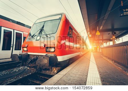 Modern High Speed Red Commuter Train At Colorful Sunset