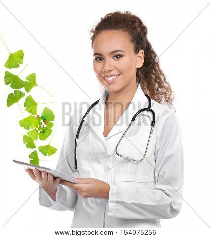 Young female doctor with tablet and Ginkgo biloba leaves on white background. Alternative medicine concept.
