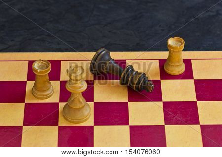 Black king falls over and resigns to show the game is over