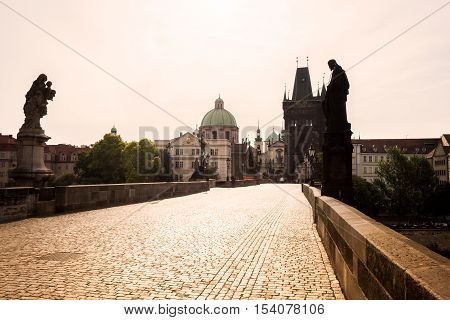 Prague, Czech Republic. Charles Bridge with its statuette, Old Town Bridge Tower, St. Francis Of Assissi Church in the background.