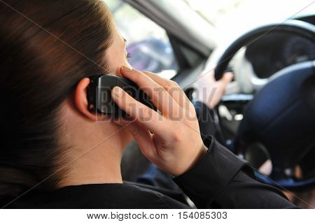 Young Woman In A Car Talking On A Mobile Phone