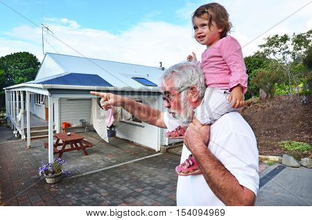 Grandfather carry his little grandchild on his shoulders.