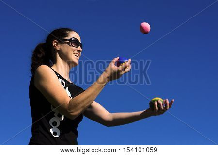 A young woman juggler is juggling balls with a blue sky background.