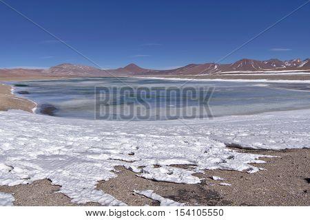 Salar de Pujsa with snow and salt water lake.