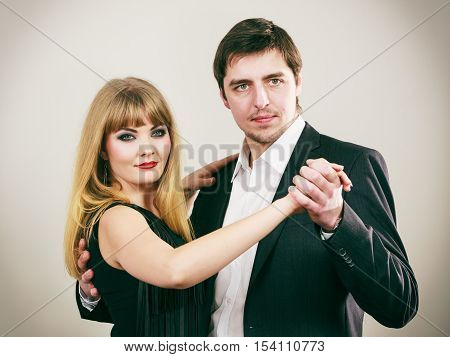 Partnership in dance. Two young elegant people dancers in motion. Gorgeous woman and handsome man dancing tango rumba waltz.