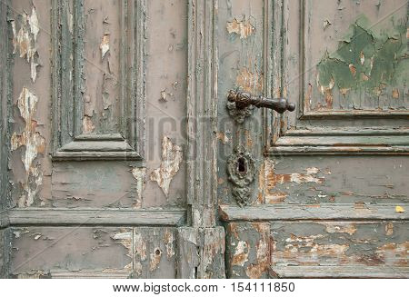 part of the old weathered wooden door with handle and keyhole