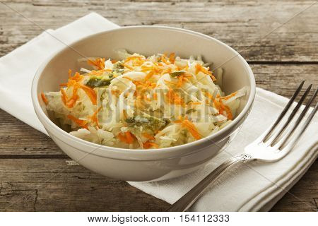 Bowl of coleslaw salad in bowl on rustic wooden table with silver fork and napkin