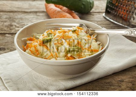 Coleslaw with fork on wooden table, carrots, cucumber and grater in background