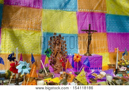 XALAPA, VERACRUZ, MEXICO - OCTOBER 28, 2016: Part of a colorful Day of the dead offering altar decorated with cut paper,windmills, food and religious figures in Xalapa, Veracruz, Mexico