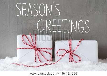 English Text Seasons Greetings. Two White Christmas Gifts Or Presents On Snow. Cement Wall As Background. Modern And Urban Style. Card For Birthday Or Seasons Greetings.