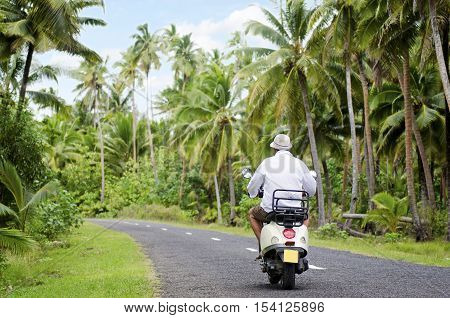 AITUTAKI - SEP 20:Tourist man drives hired motorbike on Sep 20 2013.It's one of the must popular activity in the Island but Cook Islands Driver's License is required to operate a motorized rental.