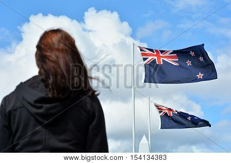 A New Zealander person (woman) under the national flags of Australia and New Zealand during a National War Memorial Anzac Day services in New Zealand.