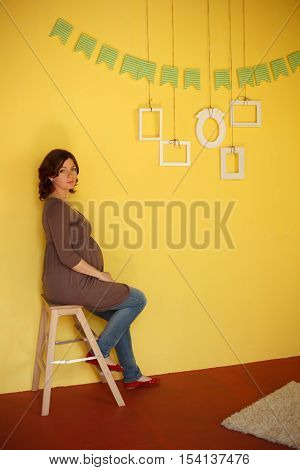 Pregnant woman sits near yellow wall with empty frames hanging on it