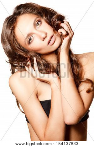 Young sensual woman portrait on the white background holds her hair in handsher head tilt to the right