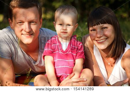 Happy family in park - motherfather and their one year old daughter on the picnic in park