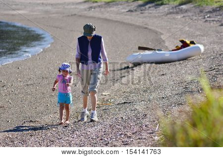 Grandmother and her grandchild walks on the beach of