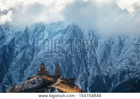 Caucasus mountains Gergeti Trinity church Tsminda Sameba against the glacier landmark of Georgia