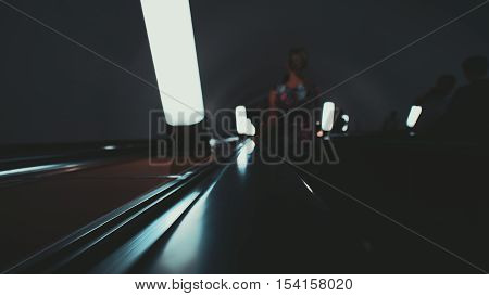 Wide blurry view of gloomy moving metro escalator way down with standing people on it