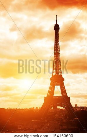 Famous landmark of Paris - Eiffel tower, Champ-de-mars, Paris, France. On sunset sky background. Photo toned in orange color