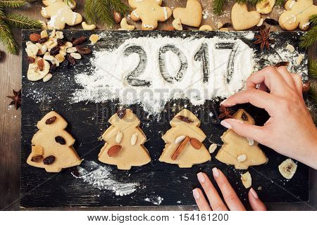 Gingerbread Christmas tree cookies and 2017 sign on flour. Confectioner hands preparing pastry for baking, Christmas treat decorating.