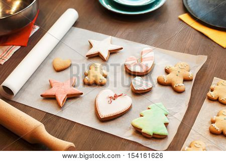 Colorful gingerbread cookies on culinary parchment. Kitchen table with traditional Christmas food. Cooking, winter, holiday, food, sweet concept