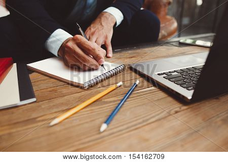Male hands writing plans in notepad. Business planning. Strategy. Development of projects.