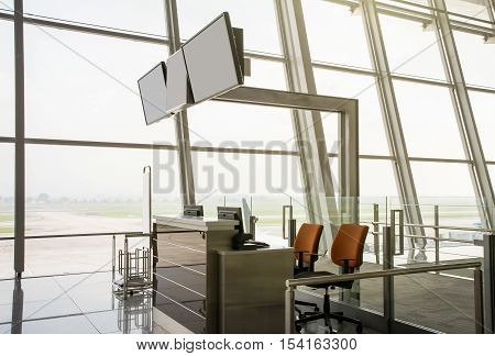 Blank monitors at departure gate. Empty departure check-in counter. Closed gate. Waiting area at airport