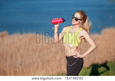 Beautiful fitness blonde girl stopped to drink water after the running. sport and work out girl in sunny day