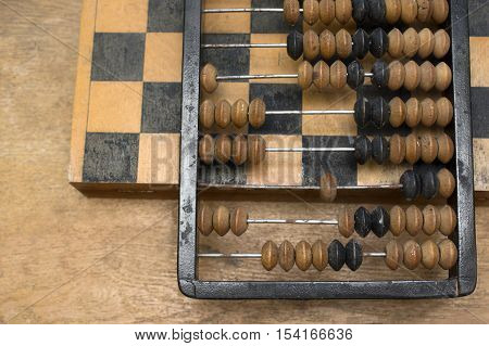 Retro accounting abacus laid on a chess overhead shot concept of business and expenses. Overhead cropped shot