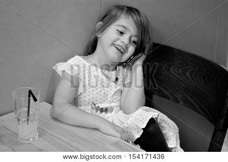 Little Girl Speak On The Phone In A Restaurant