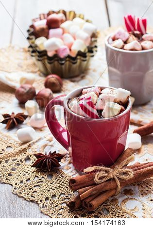 Hot chocolate with marshmallows and spices on rustic wooden table. Selective focus, tasty holidays concept. Drink for fall and winter, christmas beverage