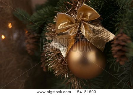 Golden Christmas ball. Closeup of gold bauble with bow hanging from decorated Christmas tree.