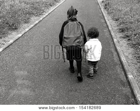 Young Sister Walks With Her Older Sister To School