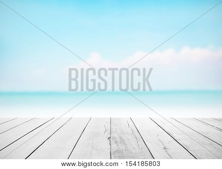 Wood floor with white blue surfing wave background. Blue cool water and sky bright with ray light. Nature blur of sea daytime. Focus to wooden in the foreground. Timber pattern texture stage
