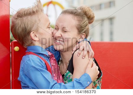 Little boy embraces and kisses his mother at playground.
