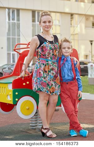 Mother and little son stand together near woodencar mounted on springs at playground.