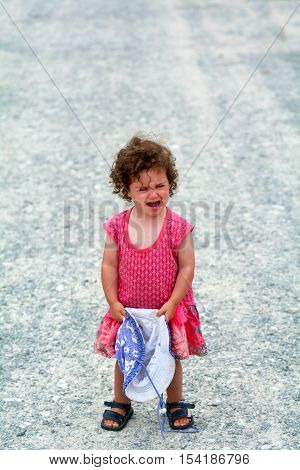Little girl (age 1-2) having a tantrum screaming alone on a gravel road during holiday travel vacation. Childhood concept with copy space