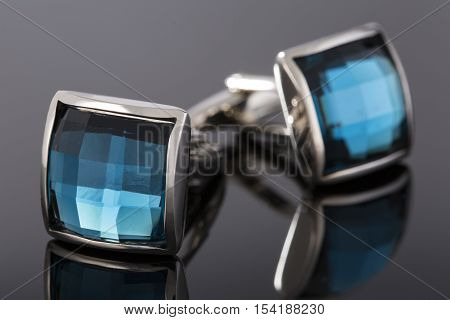 Two cufflinks made of white metal with blue stones on a black background