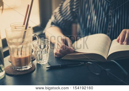 Sunday morning lifestyle scene of young hipster woman reading book in cafe with. Weekend activity or hobby concept with vintage filter effect