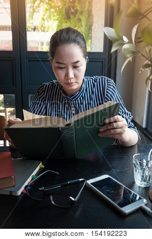 Sunday morning lifestyle scene of young hipster asian woman reading book in cafe with. Weekend activity or hobby concept