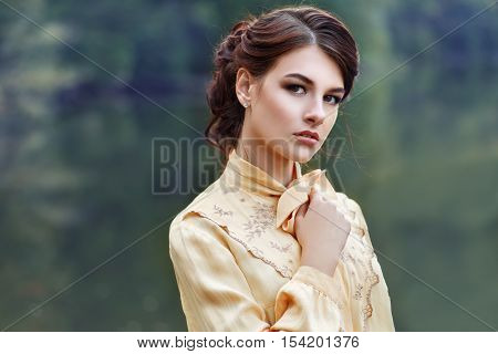 Outdoor closeup fashion portrait of sensual young stylish lady. Portrait of woman. Fashion woman with romantic. Closeup portrait of young beautiful brunette girl with brown eyes. Looking at camera