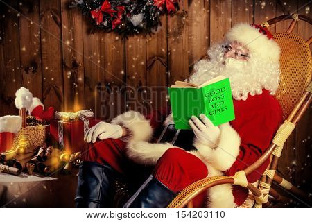 Santa Claus sitting in his wooden house in a comfortable chair and prepare gifts for Christmas. He checks his list in a notebook.
