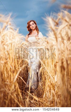 Pretty Woman Dressed In Embroidered Blouse In Wheat Field