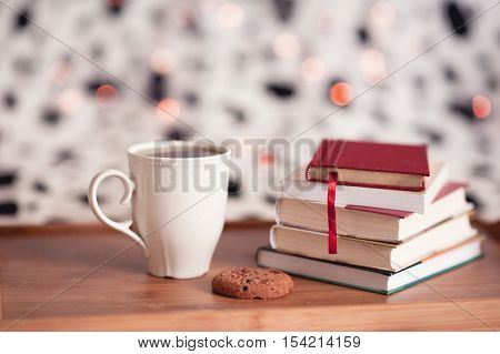 Cup of tea staying on wooden tray with cookie and stack of books over Christmas lights.