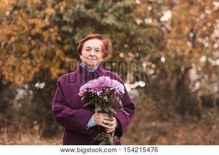 Smiling senior woman 70-80 year old wearing stylish winter jacket holding flowers outdoors. Looking at camera.