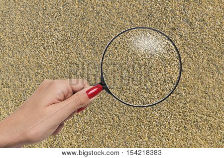 hand holding a magnifying glass enlarging grains of sand and bringing them in to focus