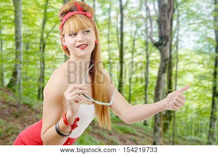 pretty young blonde girl hitchhiking in the forest