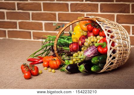 Fresh Vegetables Fruits and other foodstuffs in a wicker basket at the red brick background. Health concept