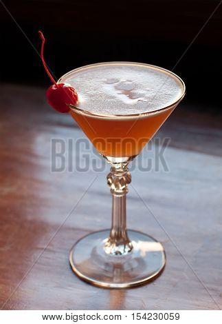 Classic cocktail Basque Martini. sloe-flavoured liqueur Patxaran, creme de bananas, fresh lime pineapple juice, Maraschino cherry. Soft focus