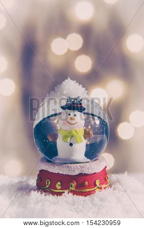 Vintage snow globe with snowman over christmas lights background